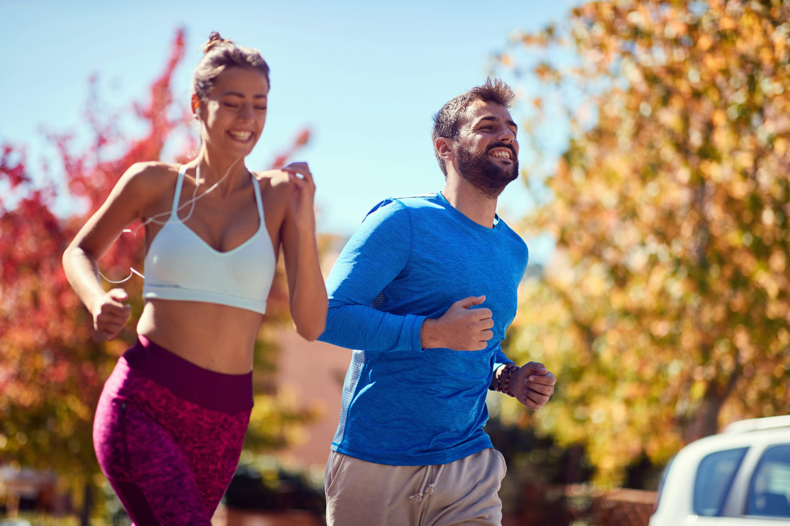 Young happy man and woman jogging at the park. healthy lifestyle.