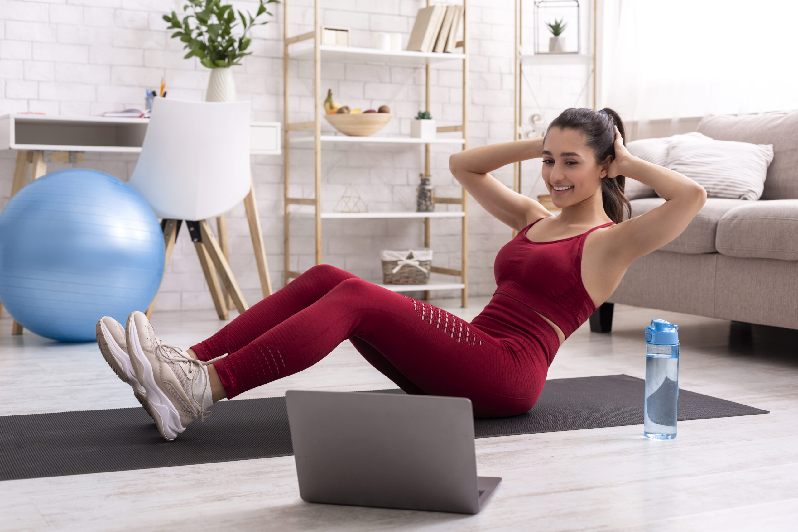 Fitness girl on her online session with personal trainer, doing abs exercises at home
