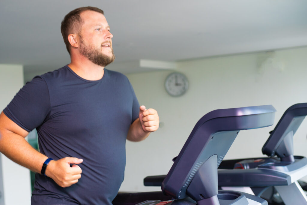 full male runs on a treadmill in a gym. concept of weight loss and sport. side view