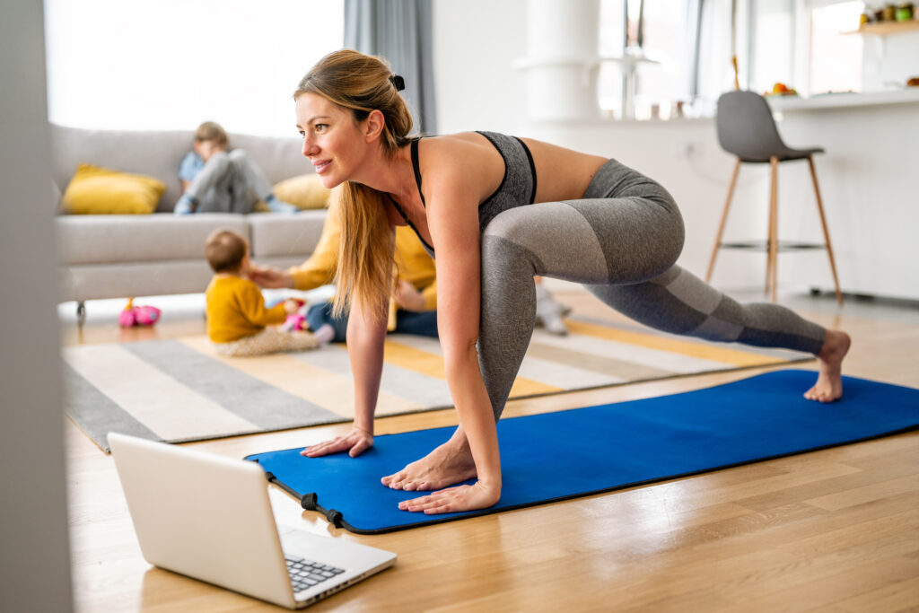 Young woman, mother is exercising at home. Fitness, workout, healthy living and diet concept.