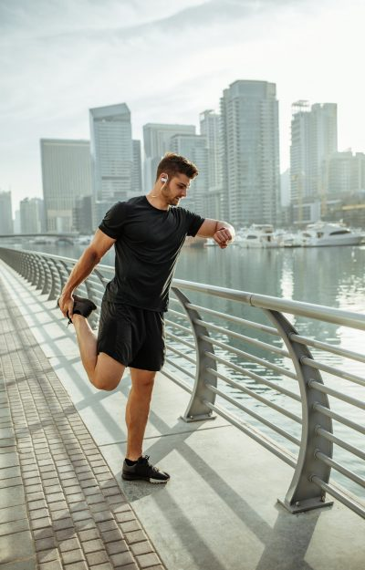 Young man warming up for a jog through the quiet city street