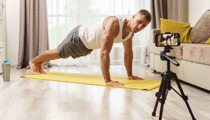 Fitness blogger is streaming or recording video for his subscribers during his home workout