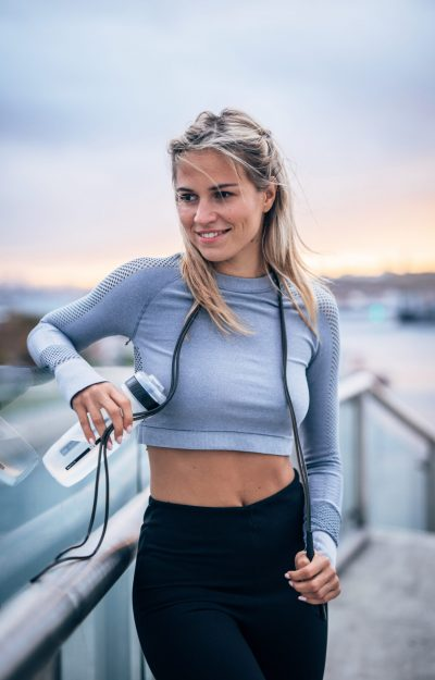 young active woman smiling after working out outside with her water bottle