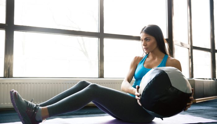 Young sports woman working out with fit ball on yoga mat at gym